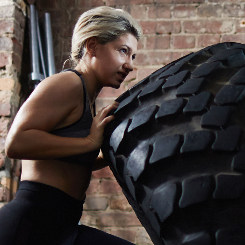a woman exercising pushing a tire